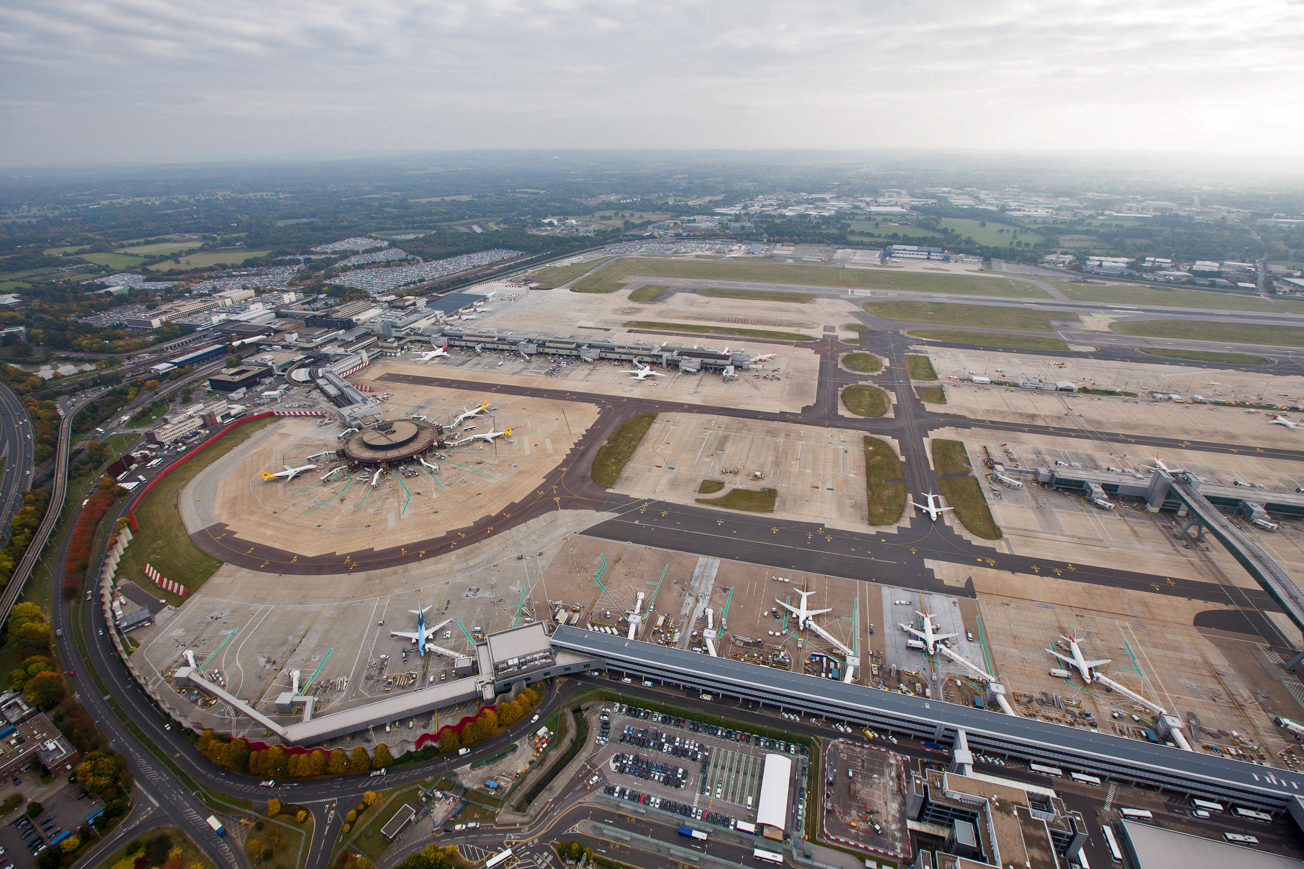Passenger aircraft sit parked at the South Terminal at London Gatwick airport in this aerial view taken over Crawley, U.K., on Monday, Oct. 24, 2016. The U.K. government will decide next week whether to expand London's main airport, Heathrow, or its rival Gatwick putting an end to decades of prevarication over what has become one of the most contentious issues in British politics. Photographer: Jason Alden/Bloomberg via Getty Images